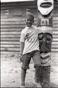 "African American boy in Spirit in Flesh t-shirt, posed next to ""totem pole"" at summer camp"