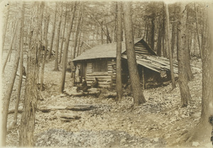 Cabin in woods with three unidentified women in front