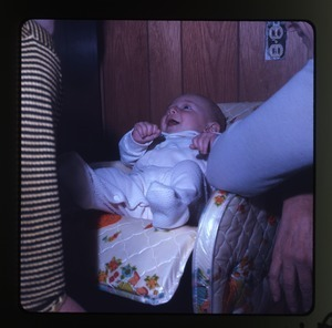 Baby (Eben) in baby seat, laughing, Montague Farm Commune