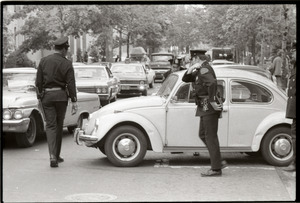 May Day concert and demonstrations: police inspecting Volkswagen Beetle used as blockade