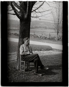 Robert Frost, seated beneath a tree, stone walls and fields in the background