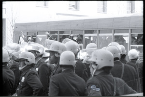 May Day demonstrations and street actions by the Justice Department: line of police in front of bus carrying off arrester protesters
