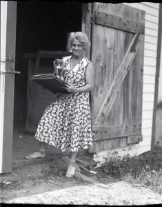 Unidentified woman (Vera Guiterman?), standing with cat and portfolio of drawings in the entrance to a barn