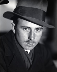 Arthur Hansen, photojournalist: close-up portrait wearing a fedora and trench coat