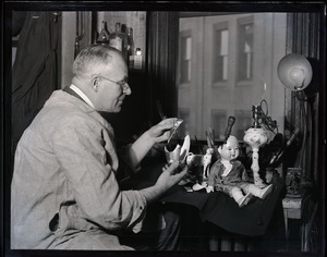 Nathan S. Hill, china repairer, working on a porcelain vase and doll
