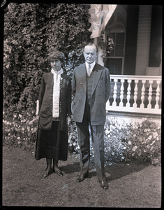 Calvin and Grace Coolidge standing in front of a house