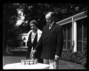 Calvin and Grace Coolidge in front of a house