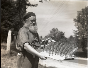 Charles Coffin, The Maine Hermit, holding folk-art sculpture of soldiers on parade