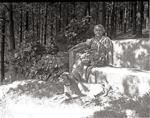 Dorothy Canfield Fisher seated on a bench outdoors, dog at her feet