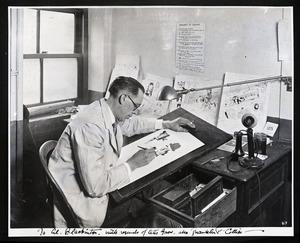Franklin P. Collier, Boston Traveler cartoonist, drawing at his desk