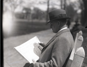 Clarence E. Jacobson, seated on a park bench, reading a copy of the Boston Herald
