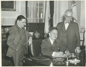Governor Bradford signing the bill to change the name to University of Massachusetts, Senator Ralph C. Mahar, and President Hugh Potter Baker looking on