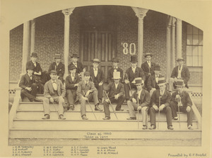 Members of Class of 1880 sitting outdoors, in front of building