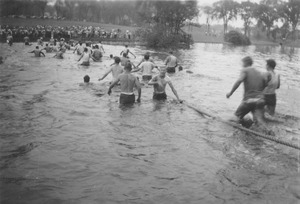 Rope pull participants wade through campus pond