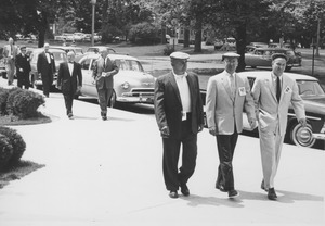 Alumni walking along on a campus sidewalk