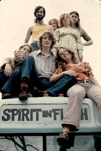 Free Spirit Press paper crew on rainbow bus. Top row: Steve Wilhelm, Gordon Adams, Julie Howard, Irene White. Bottom row: Jenny Brown, Michael Scanlon, Carol Evans