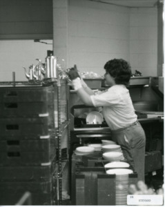 Photograph of a woman reaching for dishes, [1982-1983].