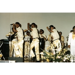 Young men in gold pants dancing, singing, and playing music on stage.