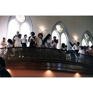 Children gathered on the balcony at the Jorge Hernandez Cultural Center in their dress clothes.