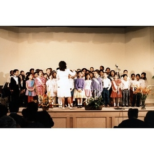 Woman conducting a group of children who are singing on stage at the Jorge Hernandez Cultural Center.