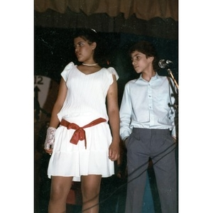 Boy and girl in dress clothes at a microphone, looking off to one side.