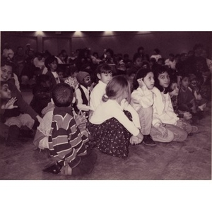 Children sitting on the floor at the Jorge Hernandez Cultural Center watch a performance.