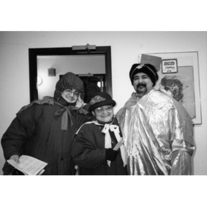 Man dressed as one of the Three Kings poses with two people dressed in winter coats and hats.