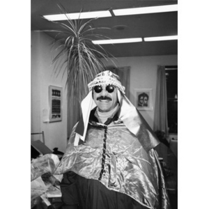 Man dressed as one of the Three Kings, or Magi, poses for a portrait in front of the office palm tree.
