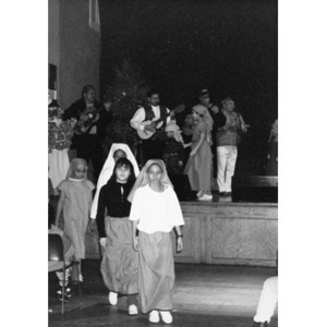 Children dressed as shepherds exit the stage during a Christmas pageant.