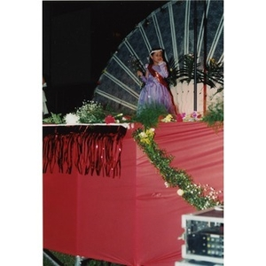 Young woman in a red dress walks across the stage during the 1998 Festival Betances beauty contest.