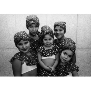 Five girls pose for a portrait wearing their folk dance costumes.