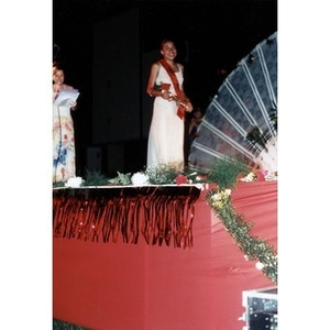 A young woman in a long white dress stands on the stage during the Festival Betances beauty contest.