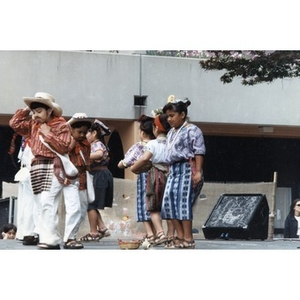 Children in traditional costumes perform on the outdoor stage at Festival Betances.