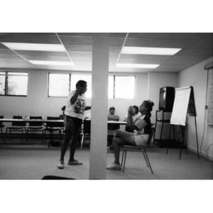 Ralph Ortiz and an unidentified female employee perform an exercise at the front of the room during a staff training session.