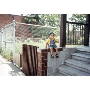 Toddler sitting on the stoop of a house eating crackers.