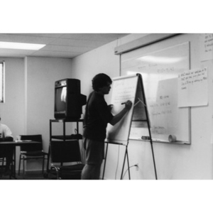 Alex Alvear writes on a flip chart at a staff training session.
