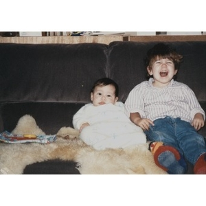 Unidentified toddler and baby on a couch.