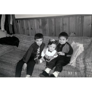 Two little boys and a toddler dressed up in their best sitting on a couch.