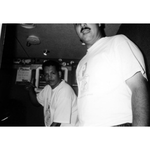 Ralph Ortiz and another man, both of them wearing Festival Betances shirts, in front of control panels, possibly in a truck.
