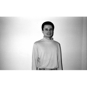 Portrait of a man in a turtleneck standing against a plain white wall.