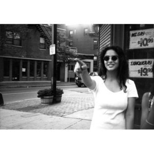 A young woman in sunglasses standing in front of a liquor store points to something down the street.