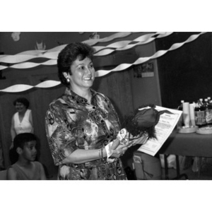 Woman holding a cloth doll and a certificate during a Child Care training program.