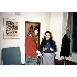 Clara Garcia speaking with a female staff member at what appears to be an office party.