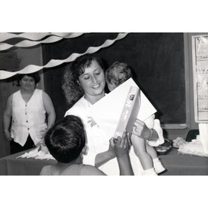 Woman holding a baby, a certificate, and a boxed puzzle during a child care training program and celebration.