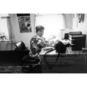 Carmen Colombani, an Inquilinos Boricuas en Acción staff member, seated at her desk in her office.