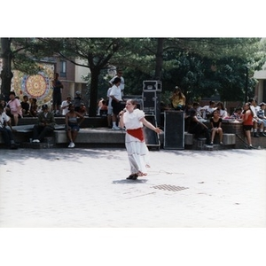 Young woman performs a song in the center of the plaza for Festival Betances spectators.