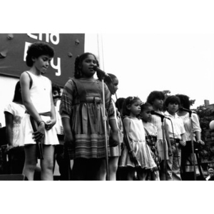 Girl at the microphone on an outdoor stage along with other children.