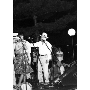 Singers on Festival Betances' outdoor stage performing at night.