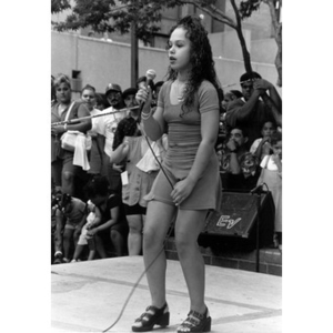 Young female singer performing on the outdoor stage at Festival Betances.