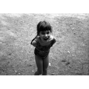 Little girl in a bathing suit laughing.